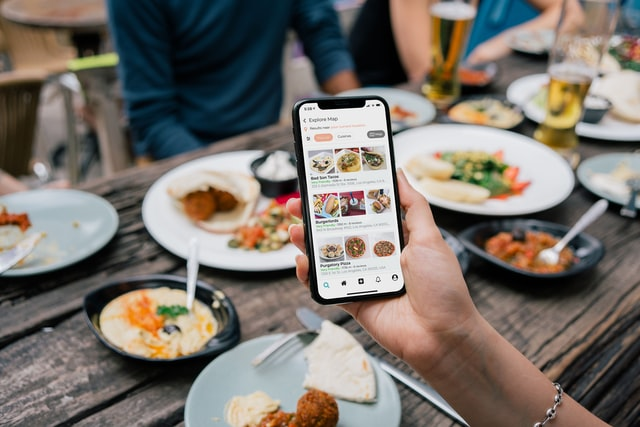 having food while looking at the food management app, food management app development services in abu dhabi, united arab emirates