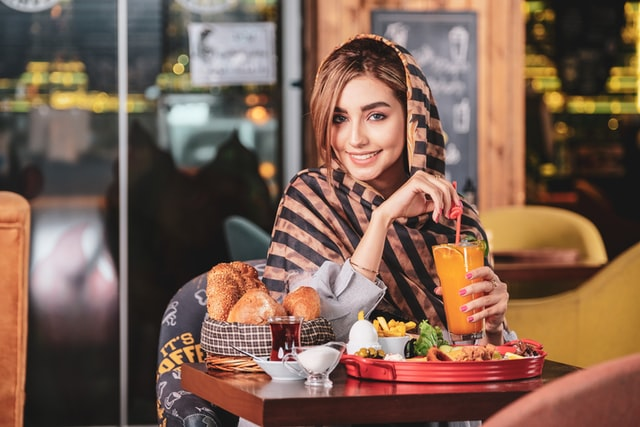 arab woman enjoying food from the restaurant in the comfort of the home, restaurant mobile app development services in abu dhabi